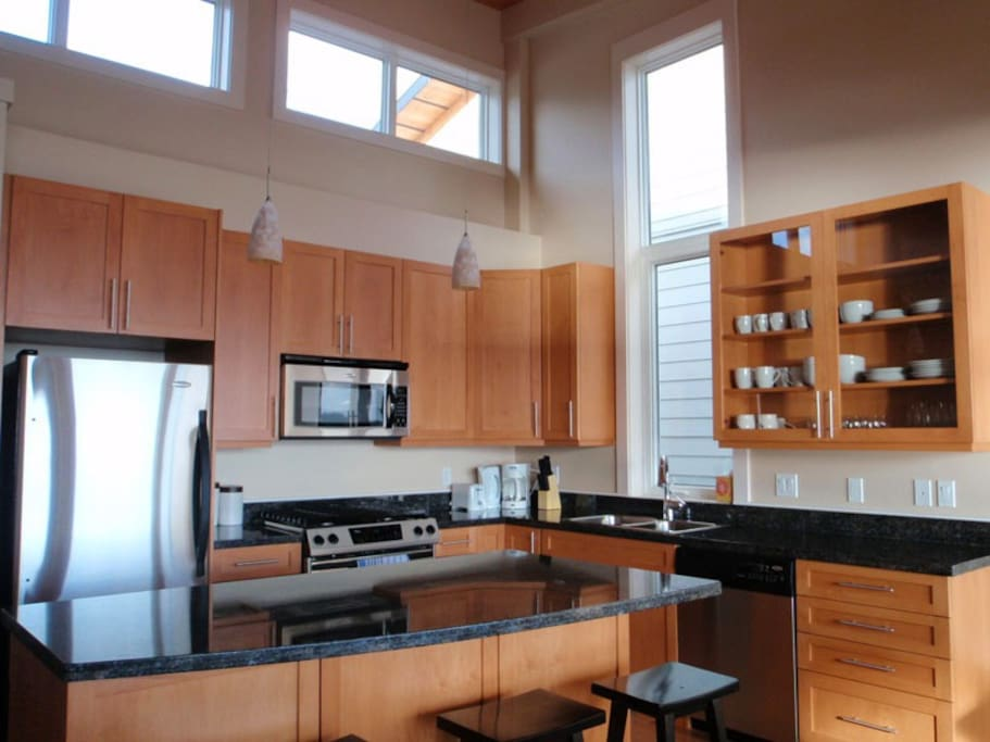 Open and well equipped kitchen with overheight ceilings throughout to host your gatherings