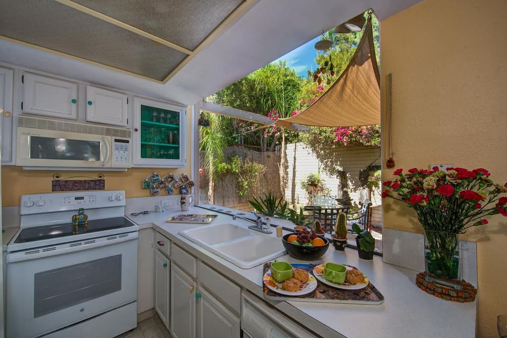 Efficient kitchen with stove, refrigerator, microwave, dishwasher (plus washer & dryer) adjoins private dining patio with sun shade.