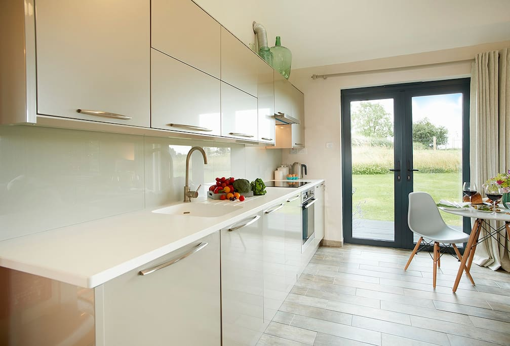 Ground floor: Open plan kitchen/dining/living area with bi-fold doors opening to private decked area