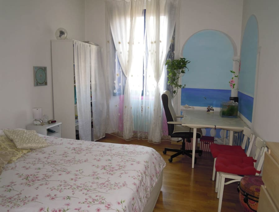 Camera da letto con scrivania e murales balcone su mare-acquario