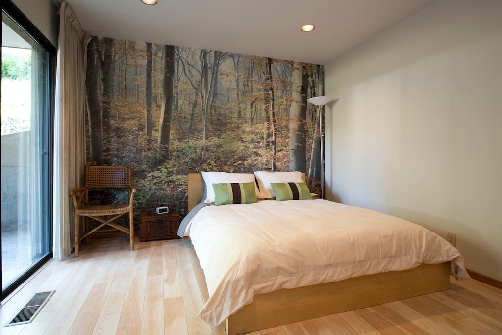 The second bedroom has a queen bed and plenty of pillows. A wooded mural behind the bed should not be confused with nature itself. We decided to leave it for guests to enjoy - 1970's at its best!