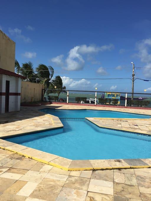 Área de lazer ampla de frente para o mar, contendo banheiros: feminino e masculino  e piscina para adultos e infantil, separaras entre si por uma grade em aço inox.