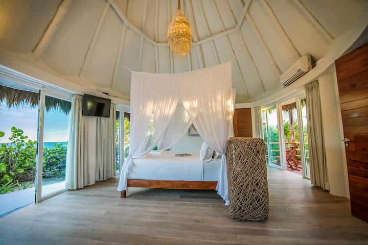 The Master suite, in its own private bungalow separated from the main house but connected by beautiful wood decking and has its own private balcony and beachfront terrace.