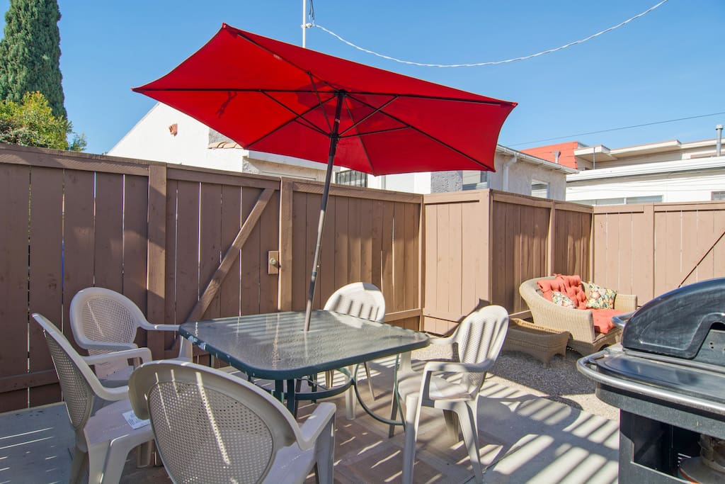Fenced backyard with patio table, umbrella, grill, and seating area.