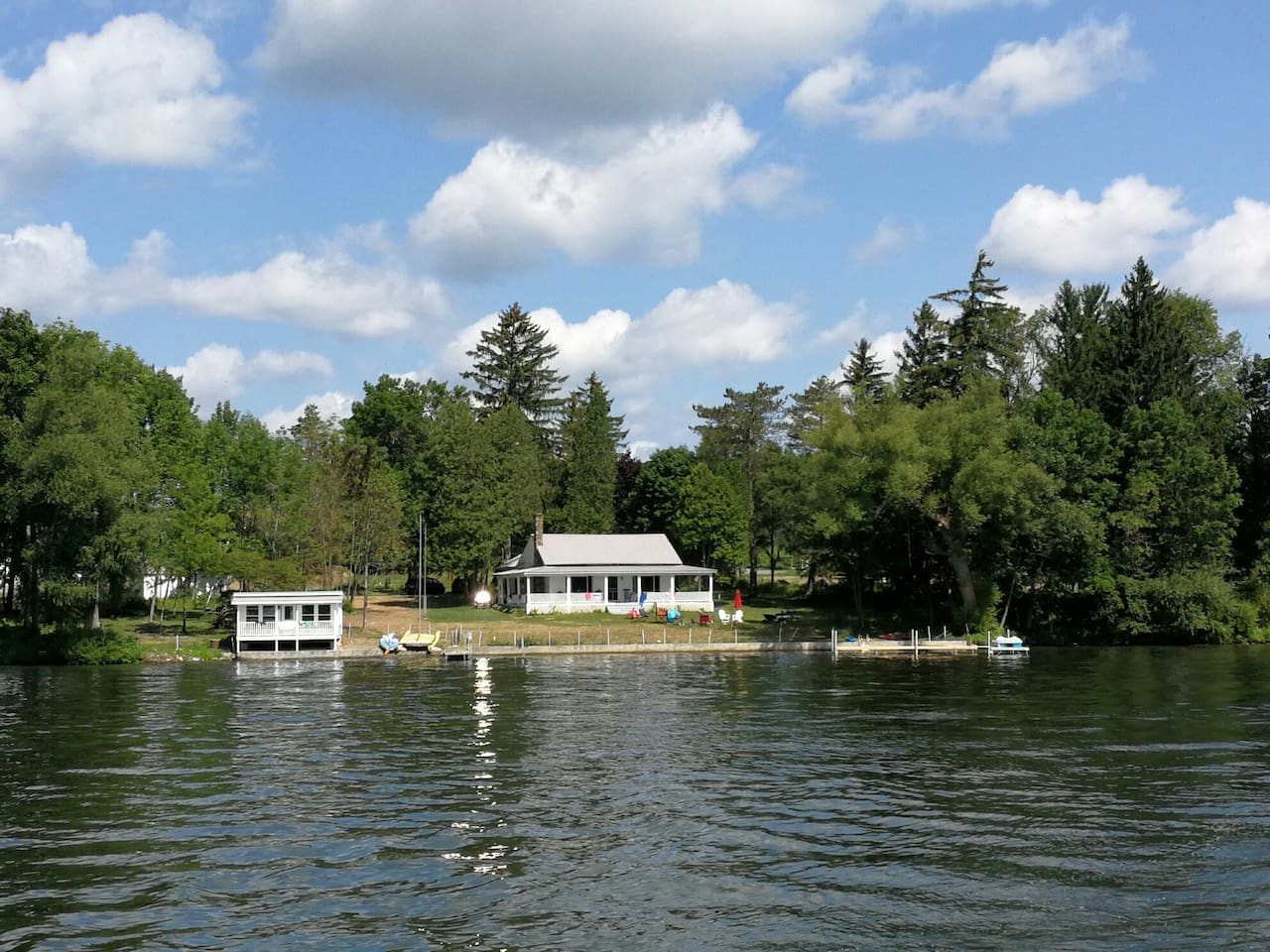 Silverlaken Lodge & Boat House as viewed from the lake. The WICKER ROOM is a private bedroom inside the Silverlaken Lodge with shared bathrooms and access to the wrap-around-deck, docks, BBQ, Fire pit, boats and other facilities at the Silverlaken Glampground.