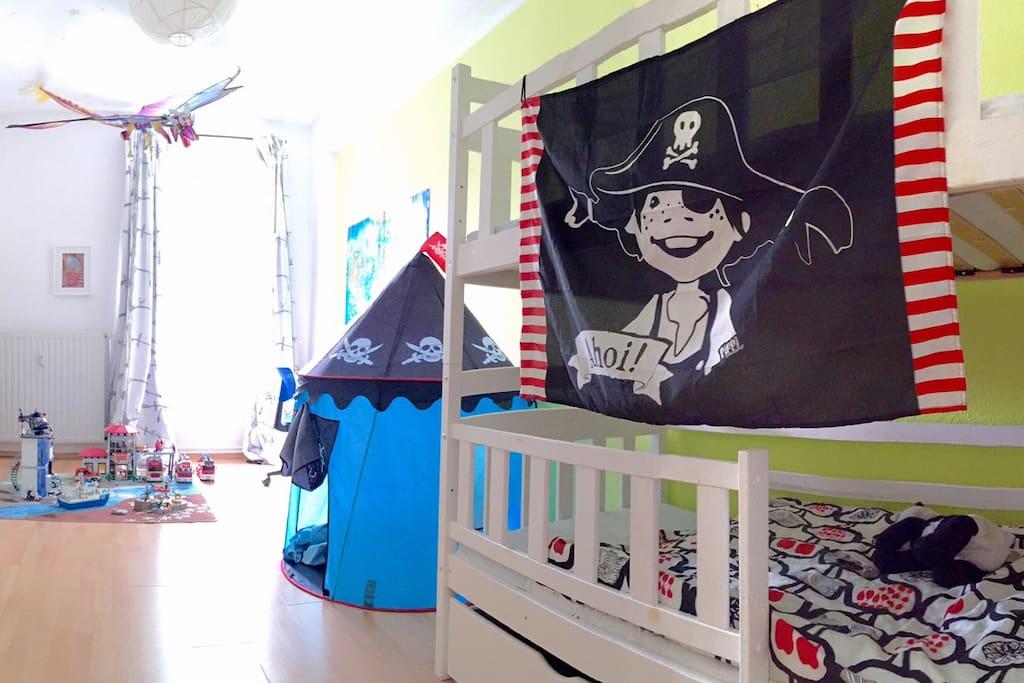 Kinderzimmer mit Hochbett, Kleiderschrank, Schreibtisch, Spielzeugregal, Spielteppich und einem gruseligen Drachen an der Decke