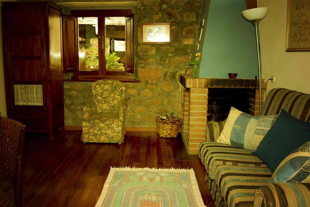 El salón con chimenea, sofá cama y tv