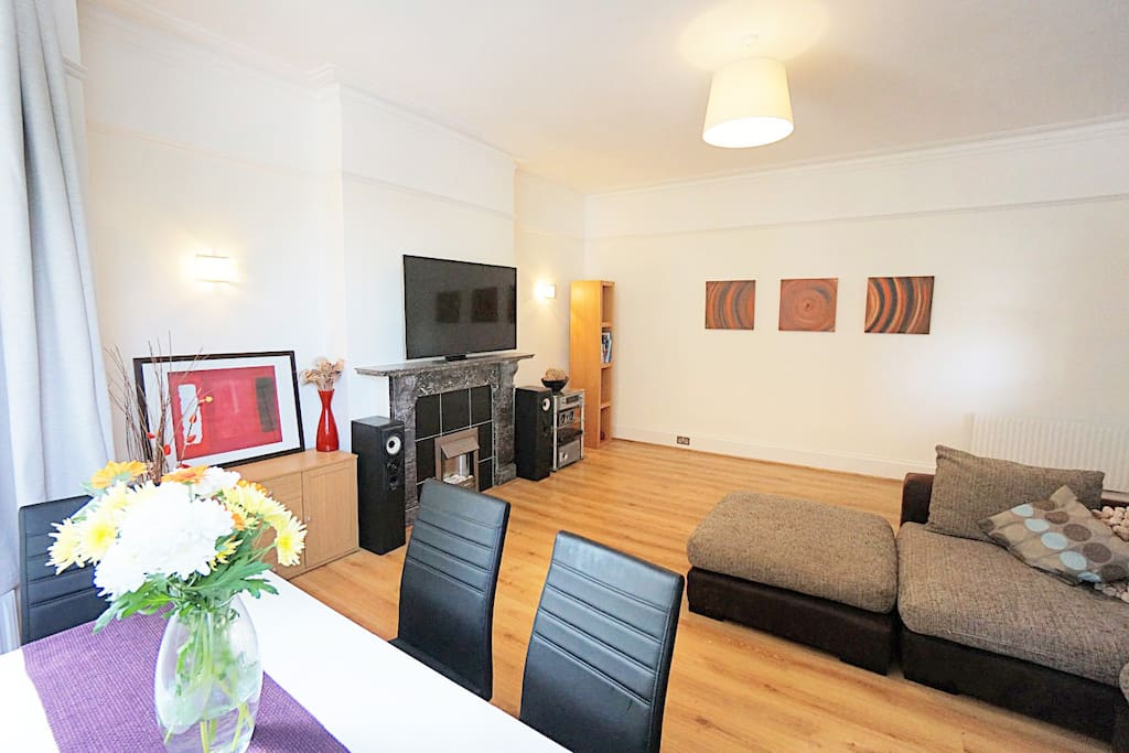 lounge with corner sofa, dining table, flat screen TV, DVD player