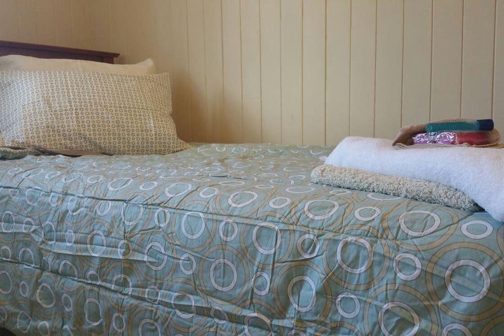 Photo of actual bed linen, towel/washer/bathmat, shampoo & body wash.