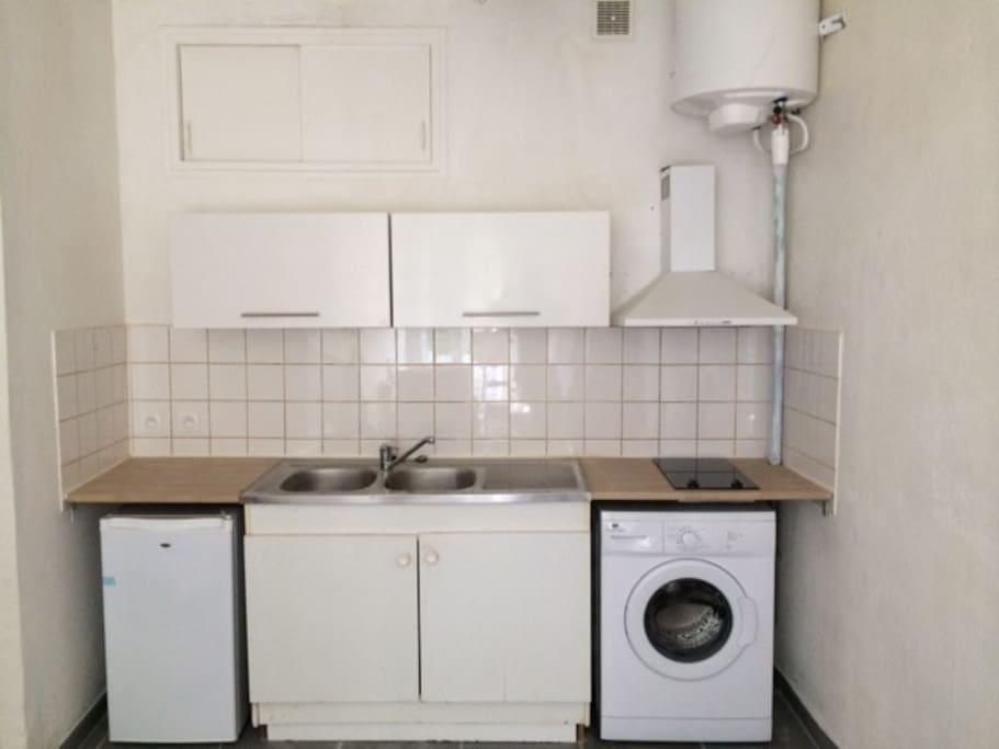 La cuisine est équipée : Lave-linge, plaques vitros, frigo, hotte aspirante.