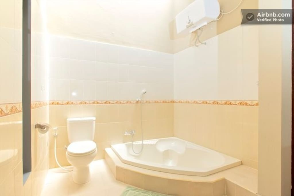 Master bedroom bathroom with bath tub and shower. Towels and soap are provided.