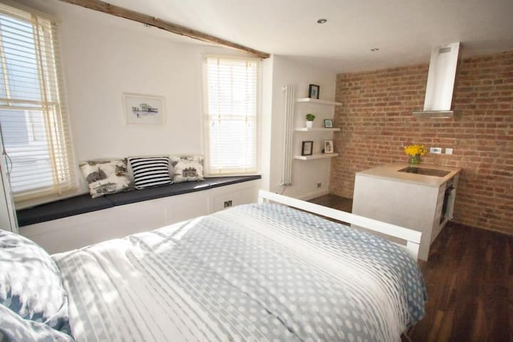 Bed with view of windows and exposed brick.