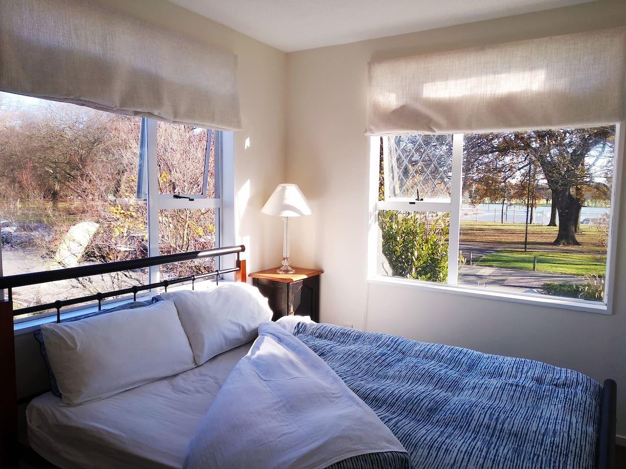 Sunny room, queen bed, cosy bedding and Hagley park views