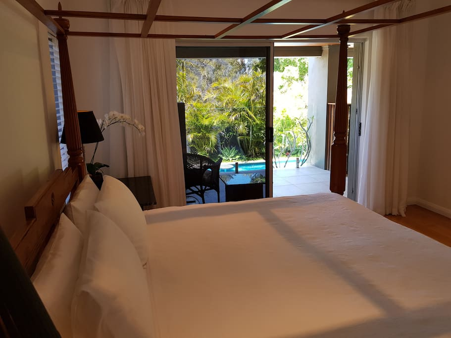 KIng four poster bed in main bedroom, has own balcony overlooking pool and tropical garden.