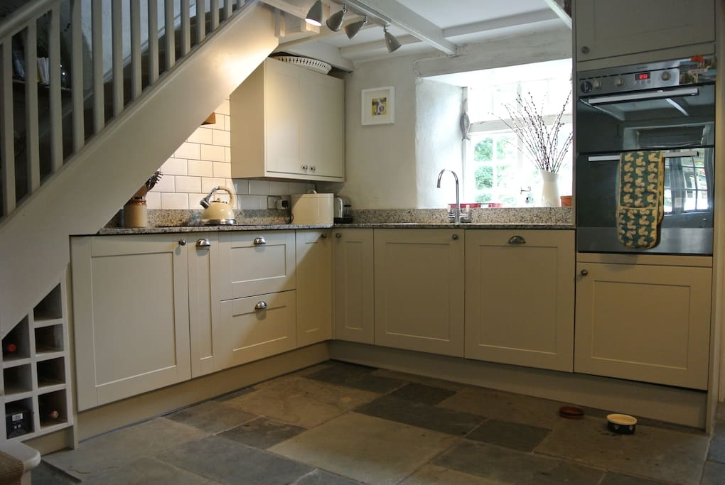 Fitted kitchen with granite worktops, hob, dishwasher, double oven and larder fridge