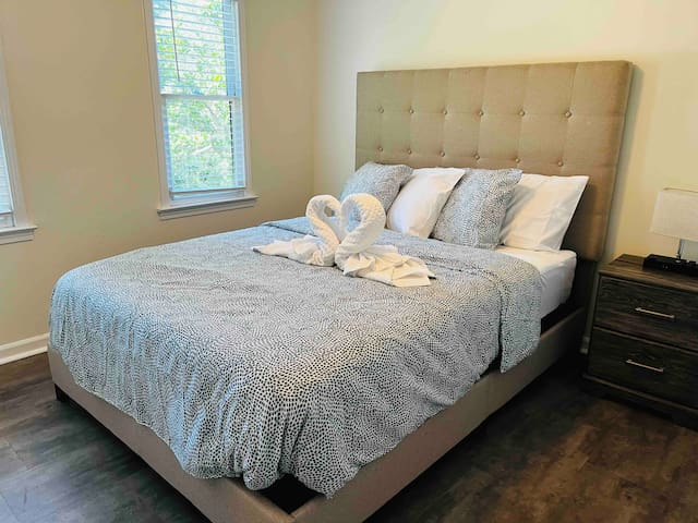 3rd Bedroom - Upholstered headboard, Queen size bed with nightstand and table lamp.