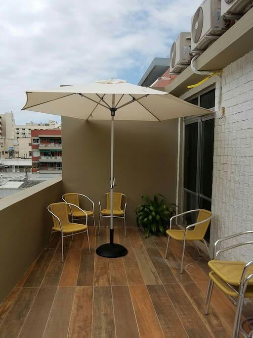Varandão com mesas, cadeiras e ombrelone.