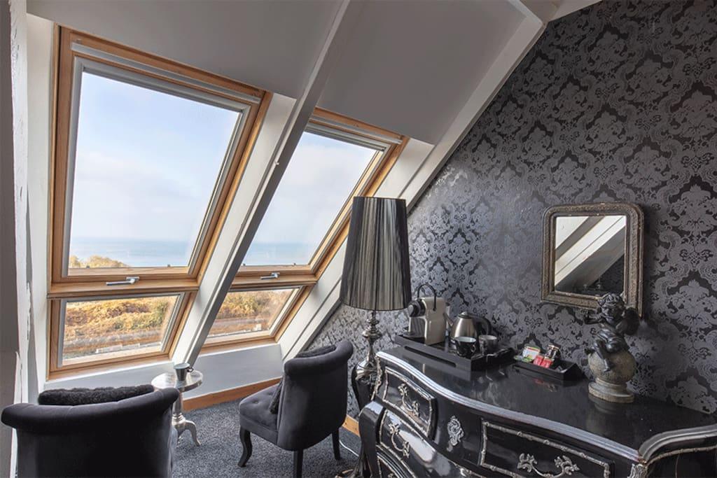 Petit salon et décoration avec vue mer depuis les fenêtre de la chambre Baccarat