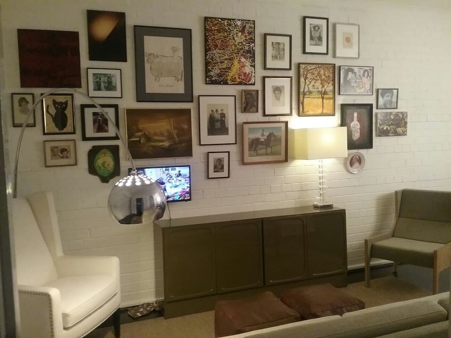 The cosy living area with TV hung amidst eclectic art.