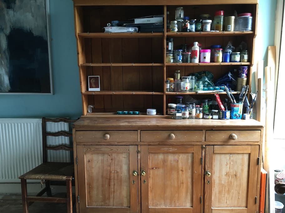Dresser with pots and paints. Half of the shelves are cleared for your use as well as the middle cupboard.