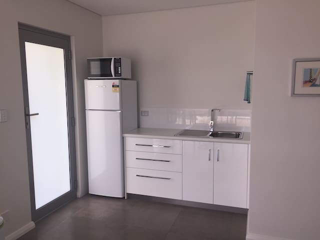Kitchenette inc full size fridge, microwave and sink. Cutlery and crockery for 4 people.