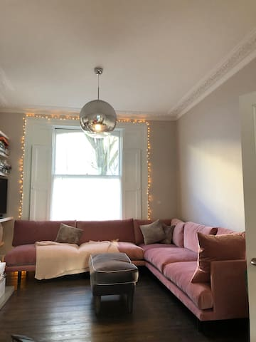 Open plan living area with corner sofa, large screen TV, open fire place and hard wood floors.