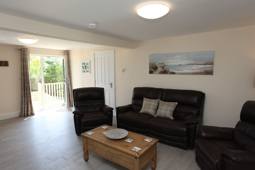 Very comfortable open plan living area with sofa and arm chairs.