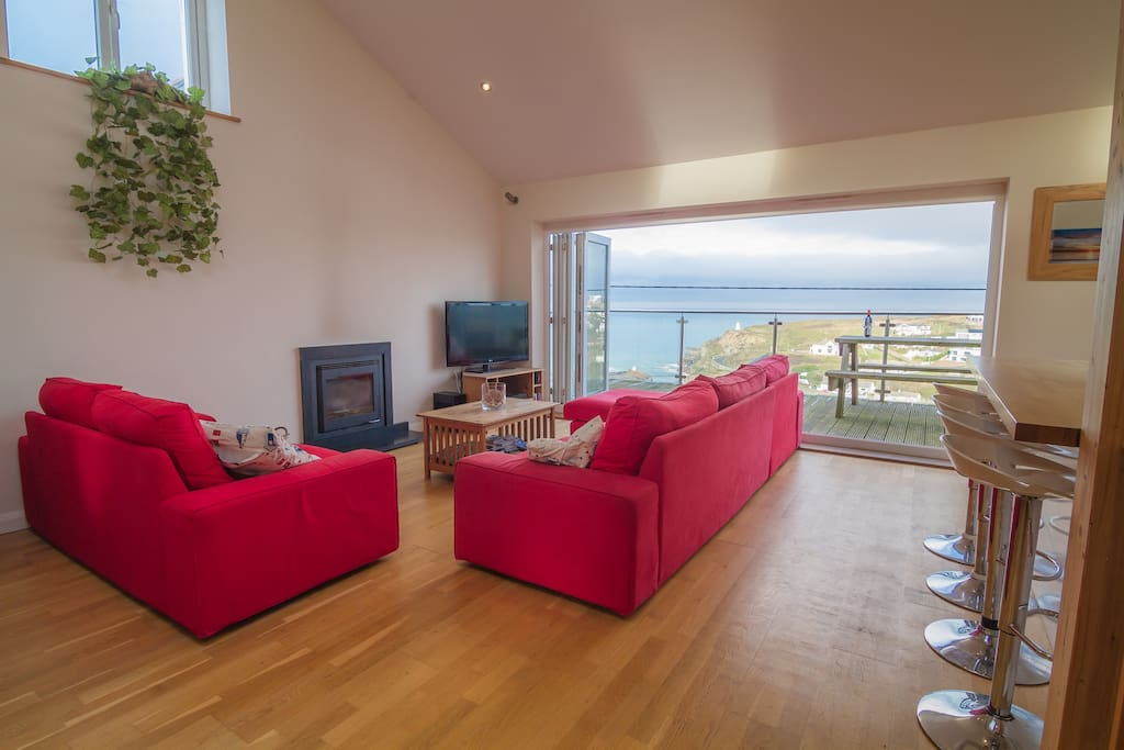 Open plan living area with bi-fold doors to sea view