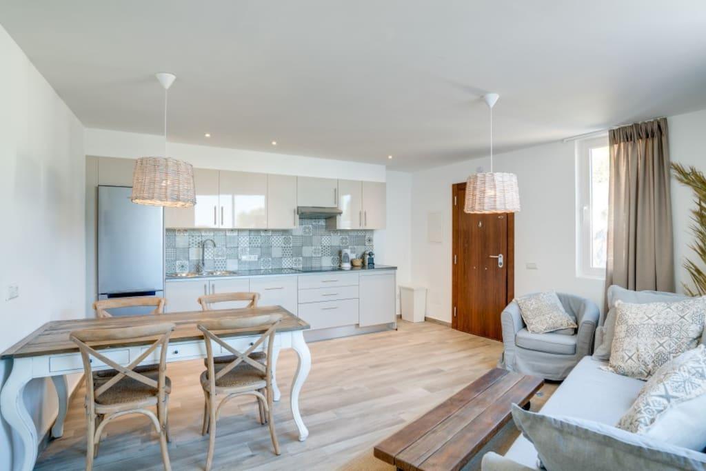 woonkamer met open keuken vaatwasser en wasmachine