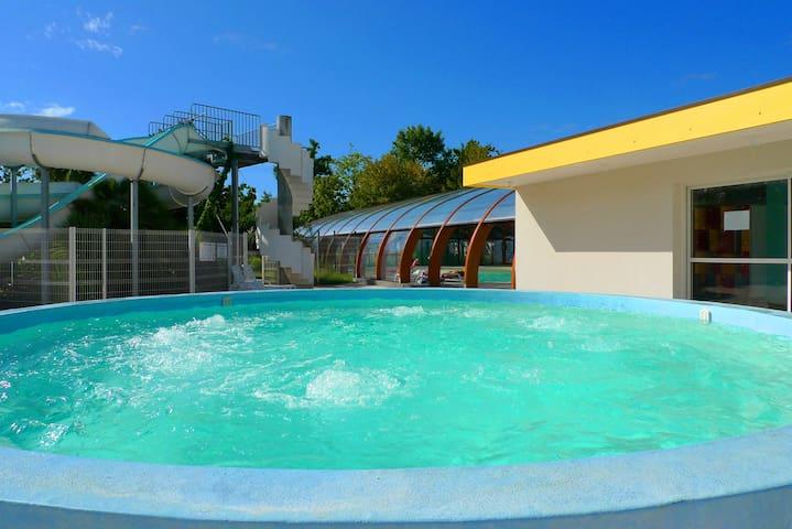 Le jacuzzi chauffé et la piscine couverte chauffée en arrière plan.