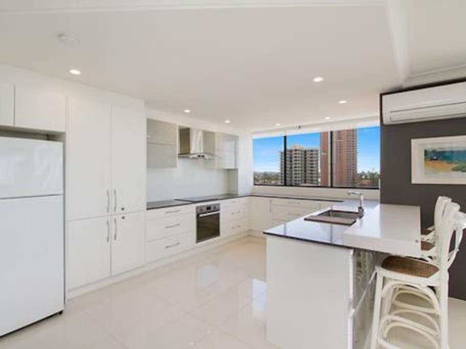 Ultra modern open plan kitchen looks out to the ocean on one side, and north to Surfers Paradise on the other side; as well as views west to Hinterland and sunning Gold Coast sunsets
