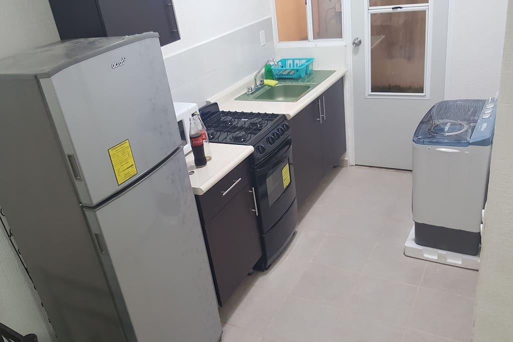 cocineta con refrigerador, estufa con horno, horno de microondas, licuadora