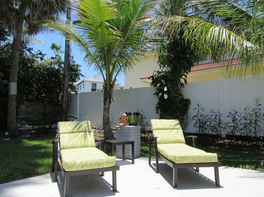 Backyard with tropical trees and cushioned chaise lounge chairs