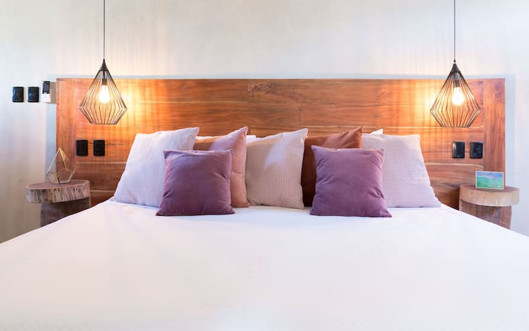 king size bed with wide spaces and artful interior design. cool place with ceiling fan and air conditioning