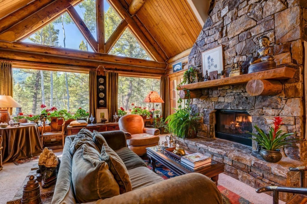 The stone fireplace may draw you into the living room, but the floor-to-ceiling windows will have you looking out.