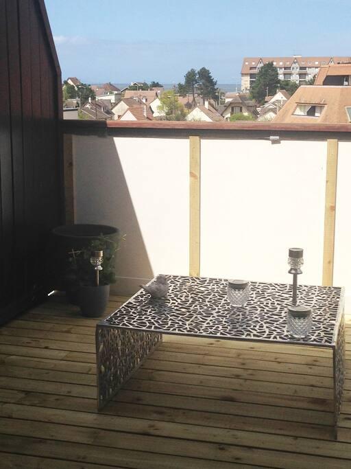 Ma jolie terrasse en bois de 9m2 où il est possible de choisir entre ombre et soleil s'illumine le soir grâce a ces lumières led qui se recharge avec le soleil permet d'entendre la mer et de manger dehors