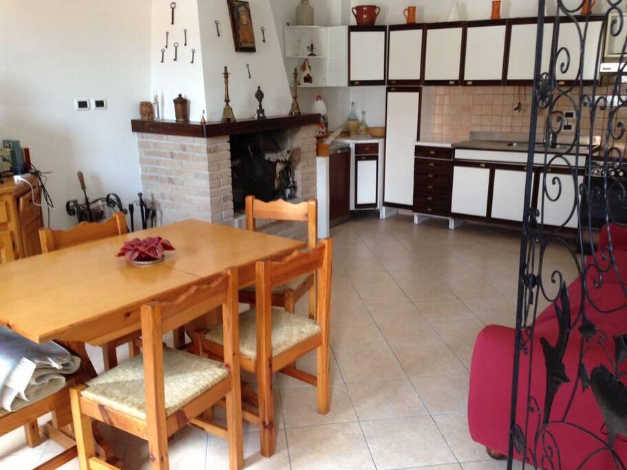 Il salotto con la cucina a vista ed il camino