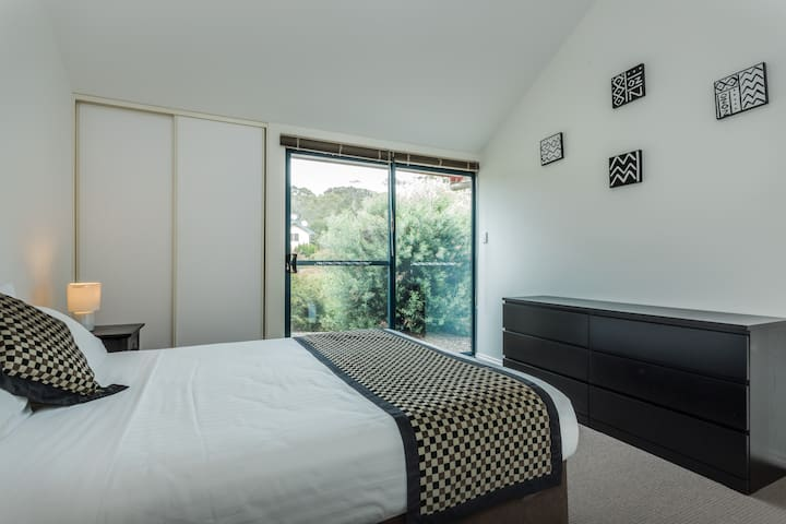 Large, airy master bedroom with Queen sized bed, high ceilings, en-suite and garden access. Enjoy high quality linen and tasteful modern decor.