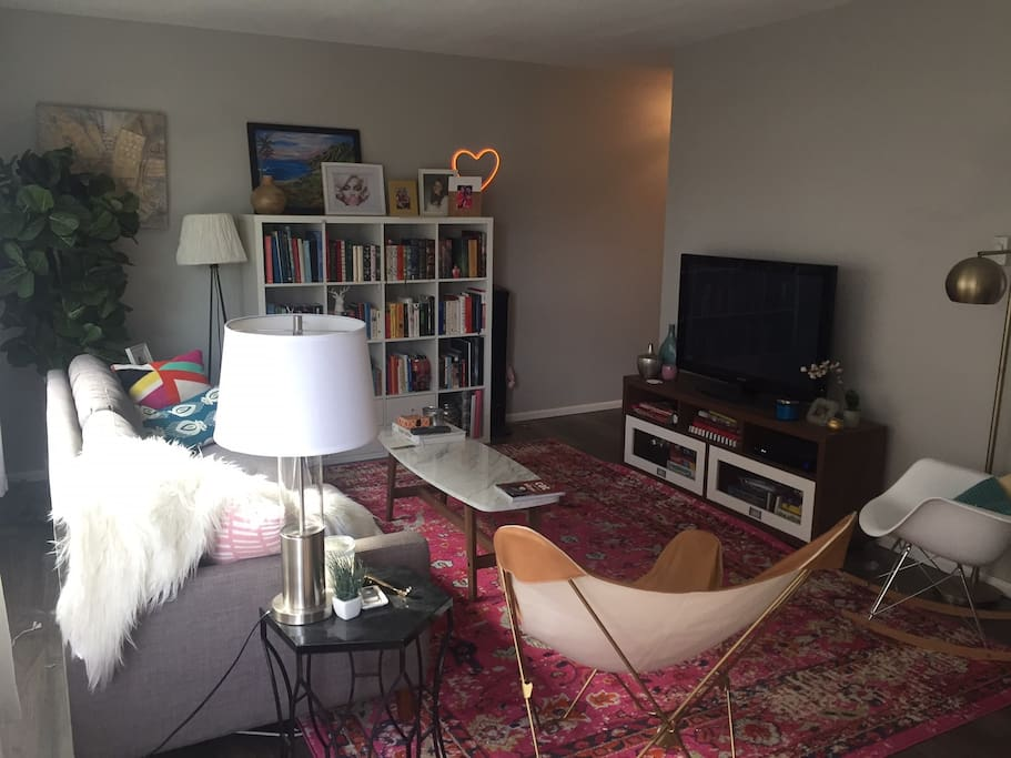 Living room has ample seating, small library, and AppleTV.