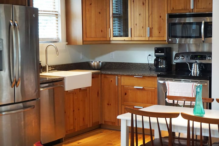 Full kitchen with modern appliances, cookware, coffee and tea