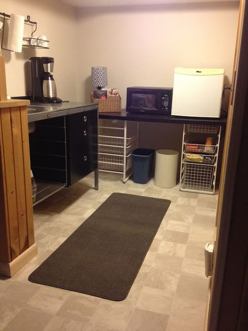 Kitchenette with small fridge and freezer, microwave, coffee maker and sink.