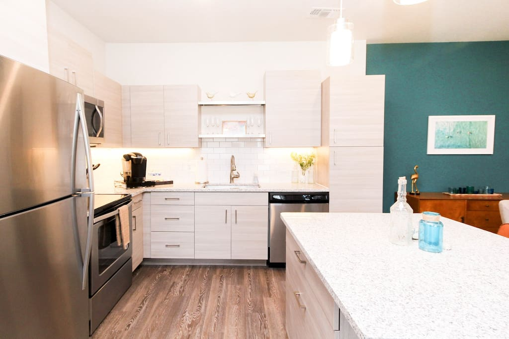 Modern kitchen with island, stainless appliances, granite countertops. A great space to entertain or dine with family.
