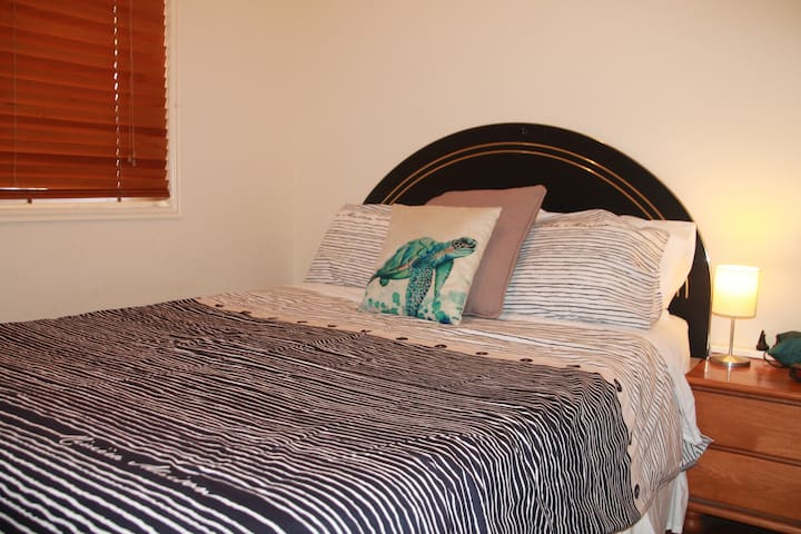 Bedroom 1. Queen bed with fresh linen and quilt cover. Bedside lamp and digital alarm clock. Pedestal fan.
