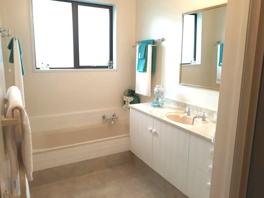 Spacious bathroom  with shower and bath and  a range of toiletries provided.