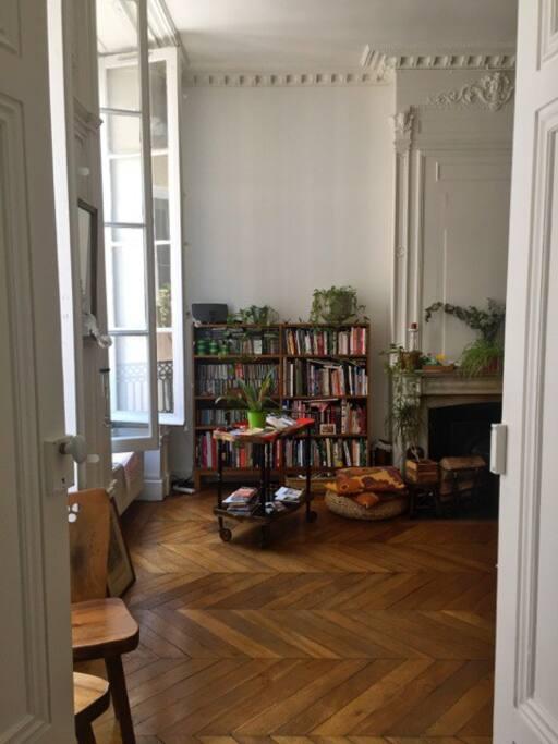 La porte de la chambre et le coin bibliothèque dans le salon
