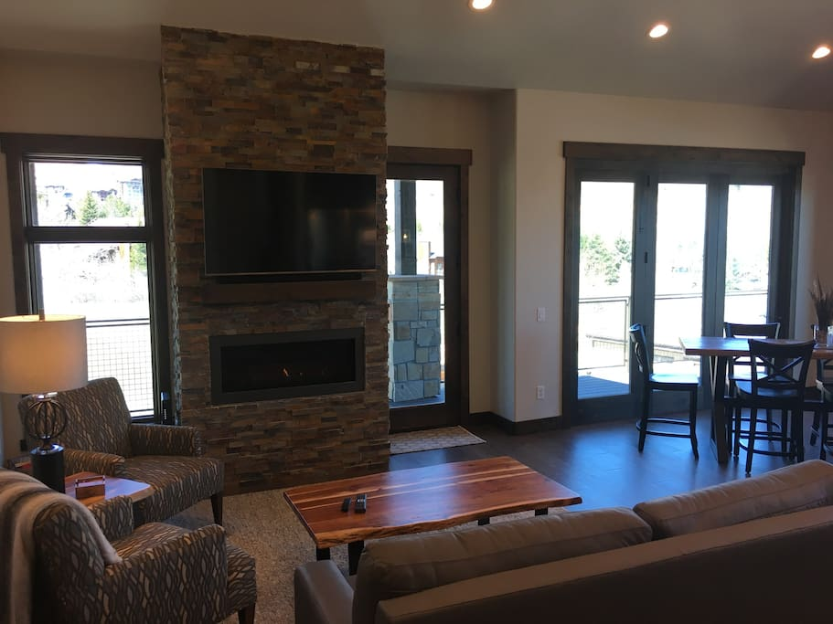 "living room with stone fireplace, 55"" flat screen, upscale furniture"
