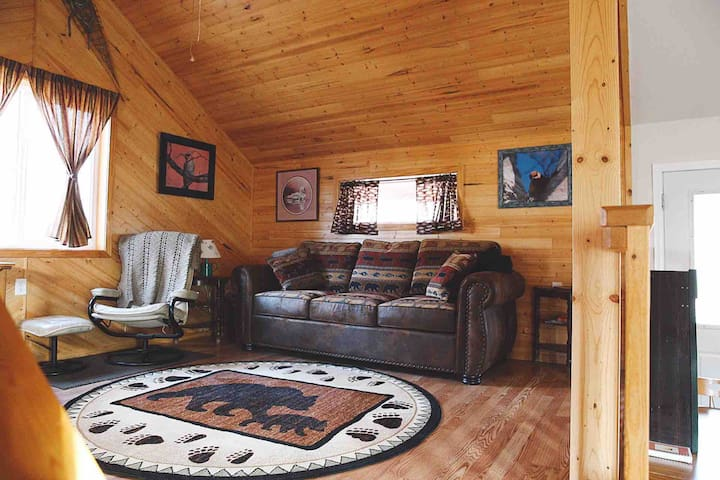 Raised living room with sofa and wood stove.