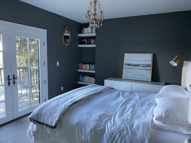 Downstairs bedroom with a king size bed and doors to a private deck