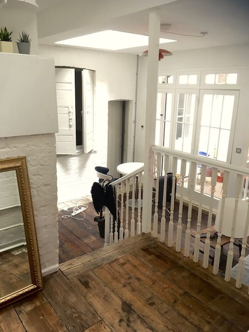 Entrance on the mezzanine. Wooden floors and white-painted brick.