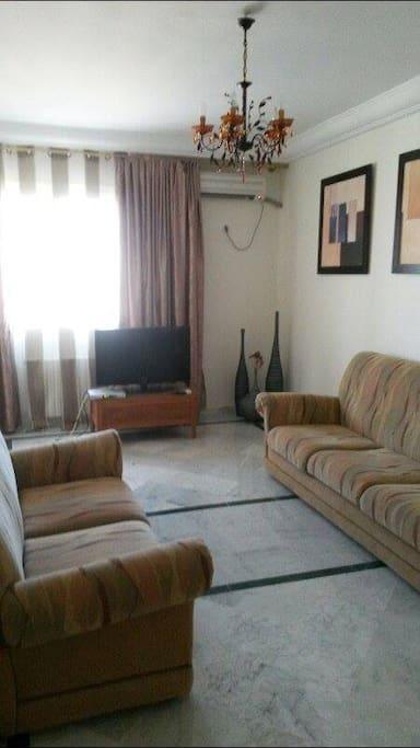 Un salon spacieux avec Tv et clim